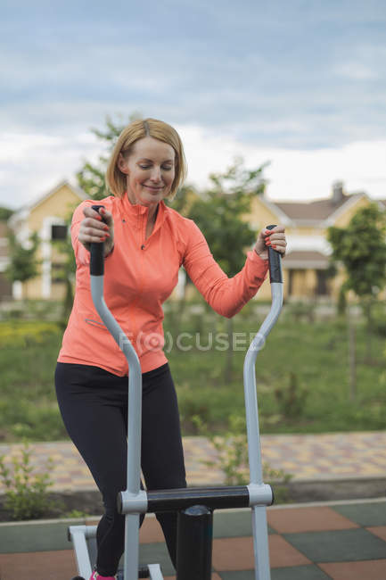 Smiling mature woman using exercise equipment in park against cloudy sky — Stock Photo