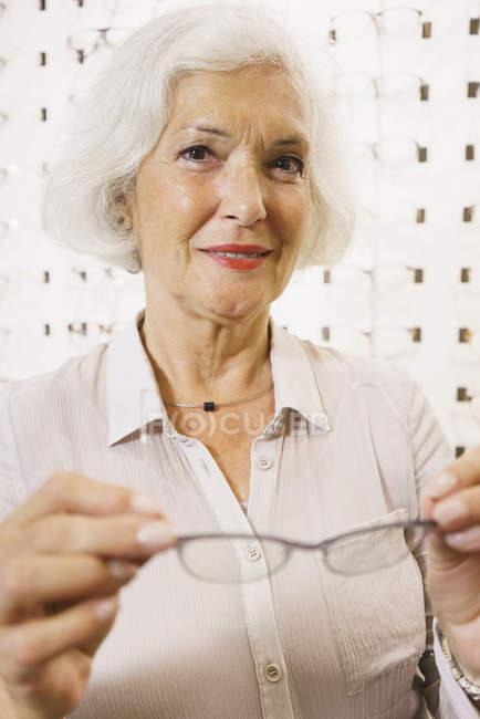 Ritratto di donna anziana sorridente che tiene gli occhiali in negozio — Foto stock