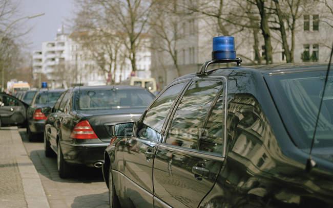 Row of police cars waiting on city street — Stock Photo