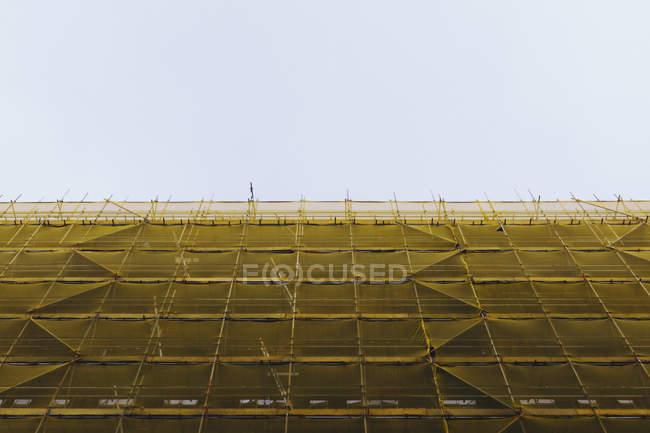 Vista exterior de la parte inferior de fachada edificio incompleto draper contra el cielo claro - foto de stock