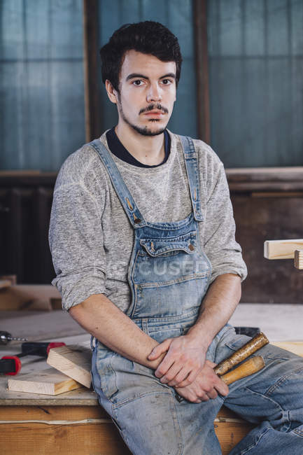 Portrait of young worker sitting with hand tools on bench — Stock Photo