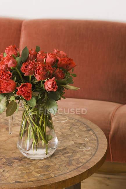 Rosas vermelhas em vaso na mesa na sala de estar — Fotografia de Stock