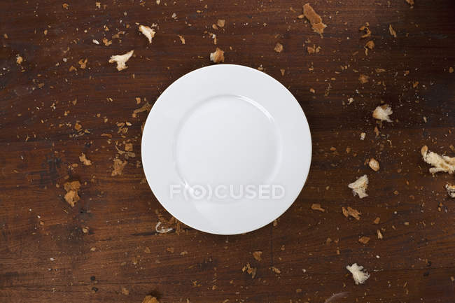 Empty ceramic plate on table with crumbs — Stock Photo