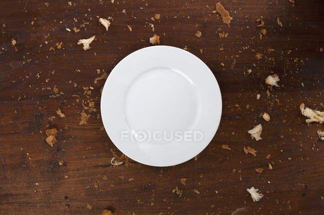 Leere Keramikplatte auf Tisch mit Krümel — Stockfoto