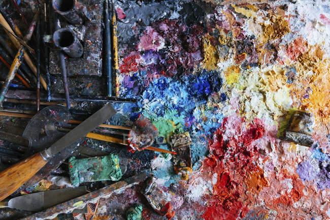 Direkt über der Ansicht der chaotischen Farben und Tuben mit Ausrüstung — Stockfoto