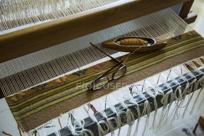 Low angle view of eyeglasses and needle on handloom weaving machine — Stock Photo