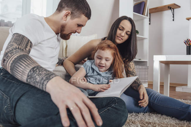 Parents looking at daughter reading book while sitting on carpet at home — Stock Photo