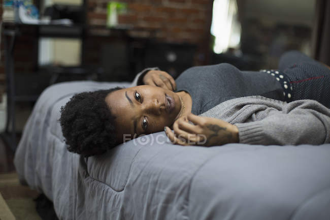 Portrait of young woman lying on bed at home — Stock Photo
