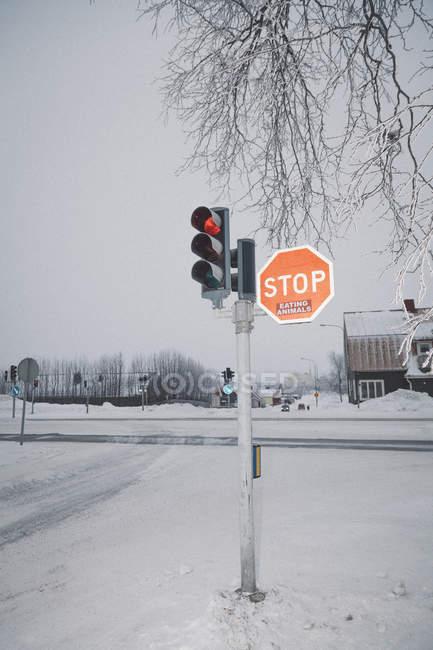 Sinal de estrada na neve paisagem coberta contra o céu — Fotografia de Stock