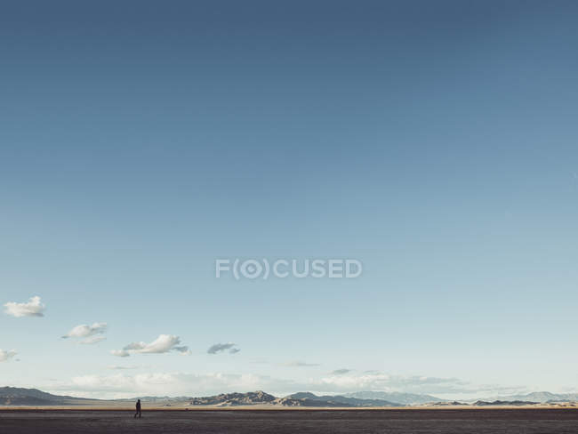 Distant view of man walking on flat over hills on horizon and gradient blue sky — Stock Photo