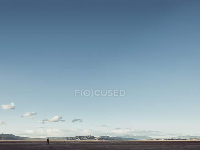 Visión distante del hombre caminando en llano sobre las colinas en el horizonte y el cielo azul degradado - foto de stock