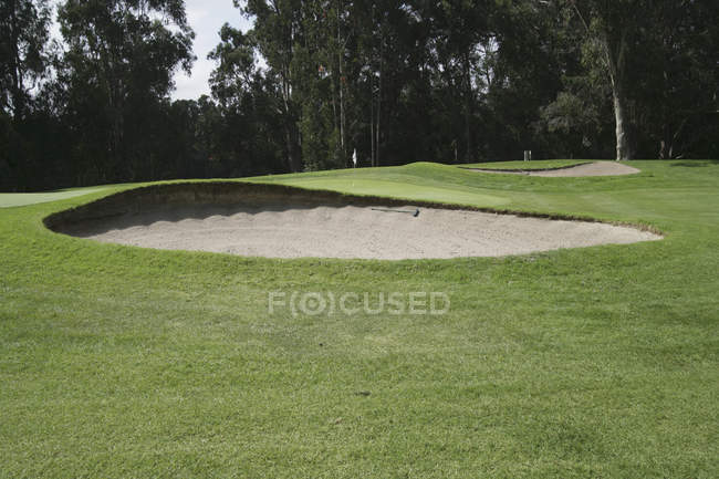Sand trap in front of green on golf course — Stock Photo