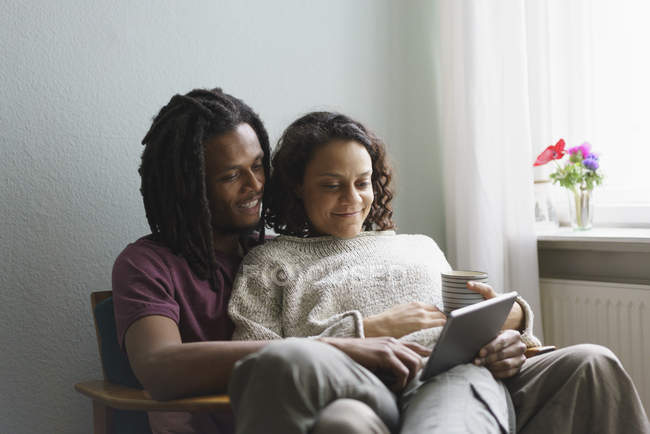 Young multi-ethnic couple using digital tablet while sitting on armchair at home — Stock Photo