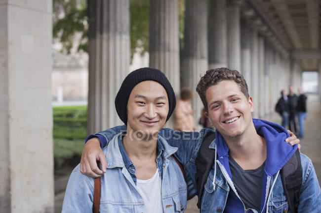 Ritratto di giovani amici maschi sorridenti in piedi con le braccia intorno, Berlino, Germania — Foto stock