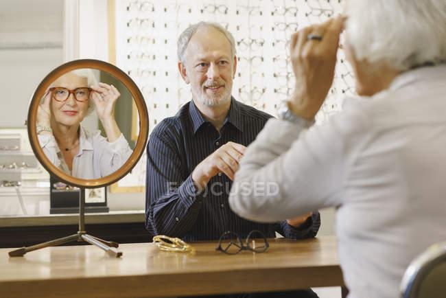Optician assisting senior woman in choosing eyeglasses at store — Stock Photo