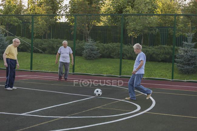 Старший друзів, які грають футбольного поля — стокове фото