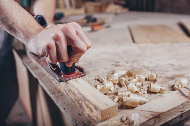 Crop carpenter hands planing wood at workshop — Stock Photo