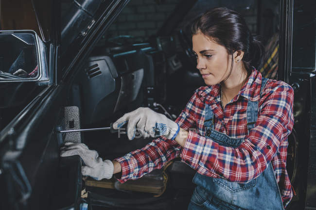 Female mechanic repairing car at workshop — Stock Photo