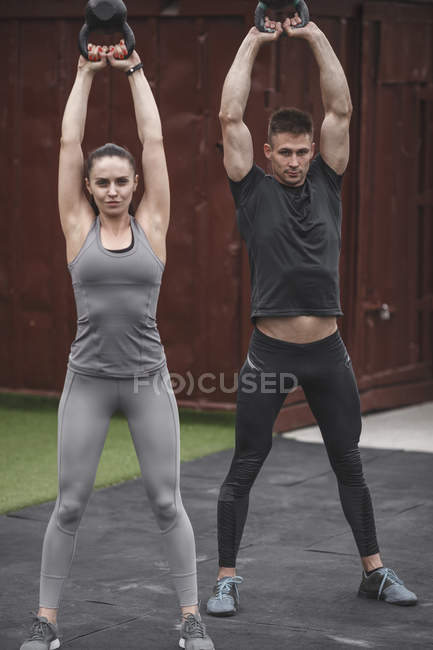 Male and female athletes exercising with kettlebells — Stock Photo