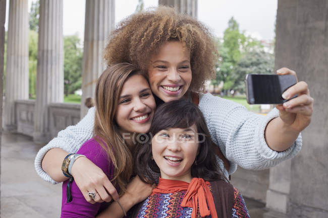 Smiling young woman taking selfie with female friends — Stock Photo