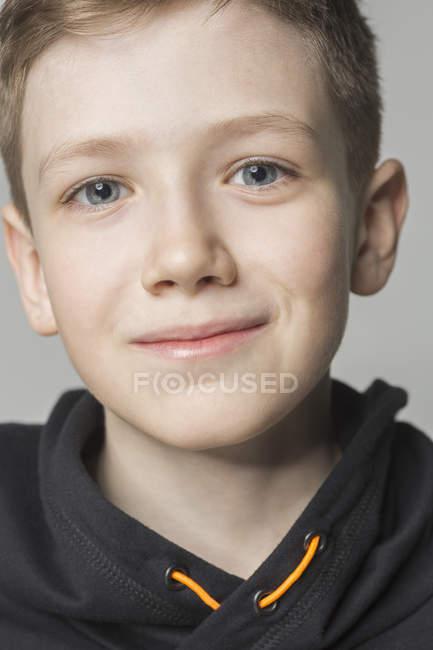 Портрет улыбающегося мальчика на сером фоне — стоковое фото
