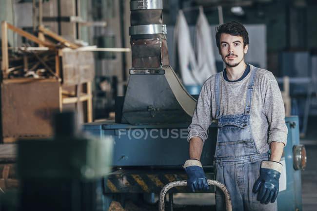 Retrato de carpinteiro em pé ao lado de máquinas na oficina — Fotografia de Stock