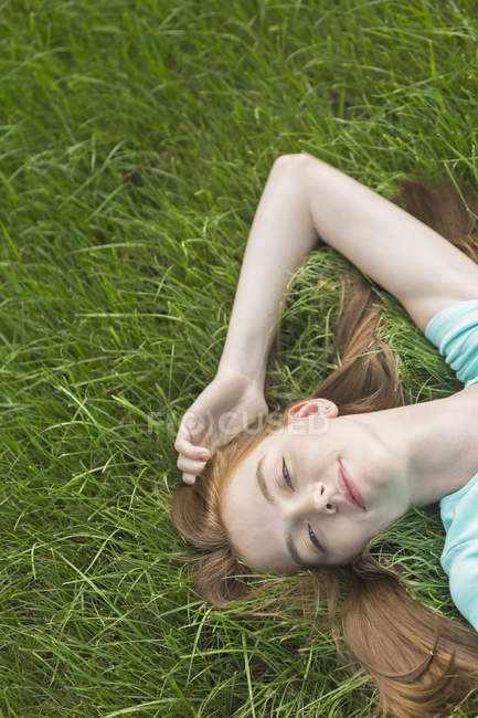 High angle view of beautiful woman lying on grassy field — Stock Photo