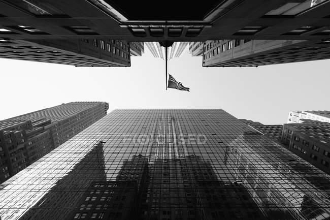 Безпосередньо під видом з американським прапором серед хмарочосів проти неба, Нью-Йорк, Нью-Йорк, США — стокове фото