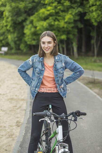 Портрет усміхається жінка з руки на стегна, сидячи на велосипеді в дорозі в парк — стокове фото