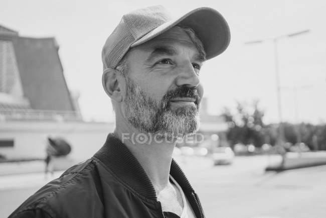 Pensativo sorrindo homem maduro vestindo boné olhando para longe no dia ensolarado — Fotografia de Stock