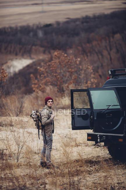 Ragionevole escursionista portando zaino e in piedi accanto al bagagliaio auto aperta — Foto stock