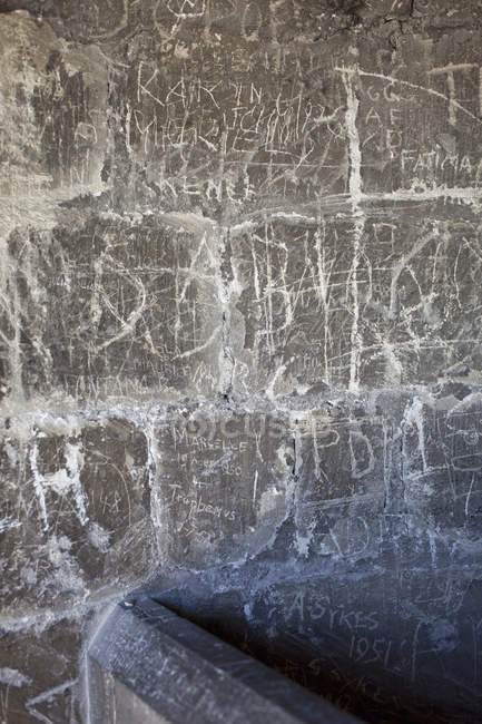 Handwritten graffiti etched into stone wall — Stock Photo