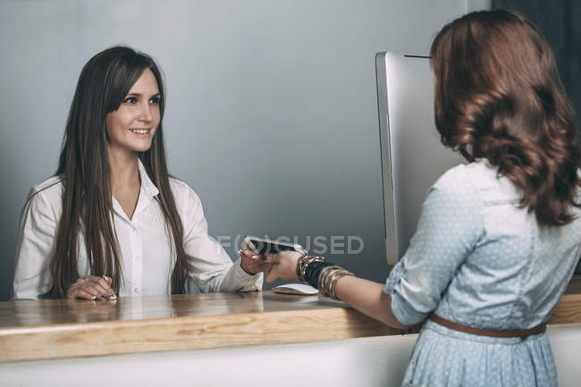 Young saleswoman handing repaired smart phone to female customer at counter — Stock Photo