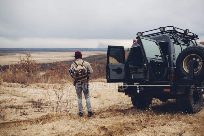 Rear view of hiker standing by sports utility vehicle on barren land against sky — Stock Photo