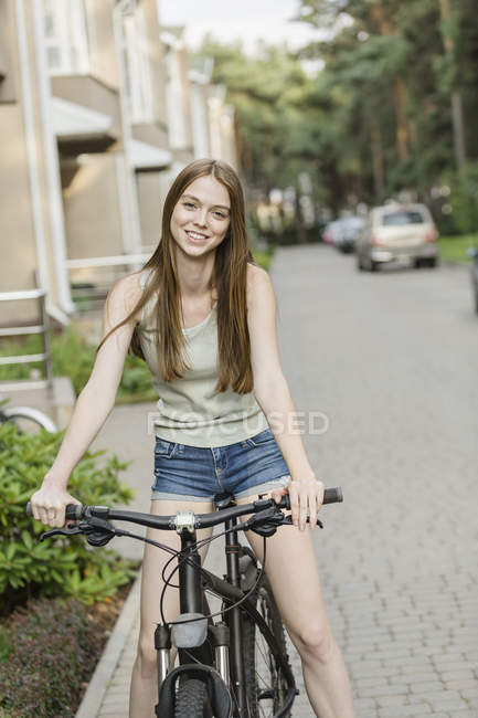 Smiling woman cycling on cobbled street against buildings in city — Stock Photo