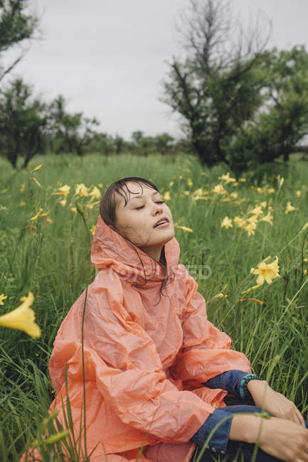 Young woman relaxing amidst yellow flowering plants during rainy season — Stock Photo