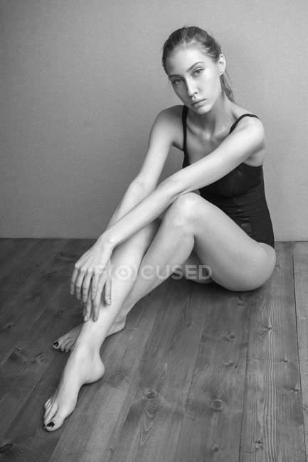 Портрет уверенной женщины в трико, сидящей на деревянном полу у стены — стоковое фото