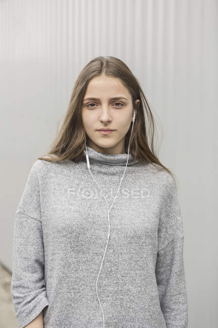Portrait of teenage girl listening to music with earphones against wall — Stock Photo