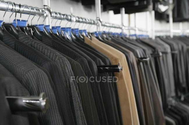 Row of business suits on clothing store rack — Stock Photo