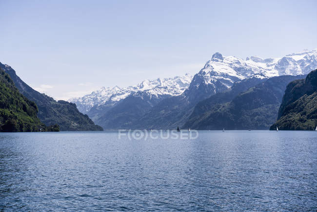 Scenic view of lake among snow capped mountains over blue sky — Stock Photo