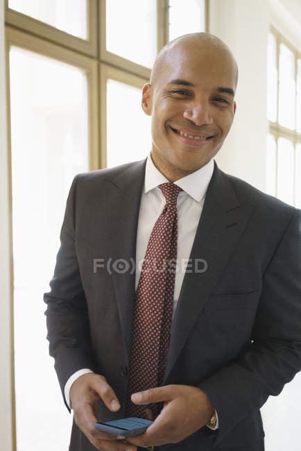 Portrait of Confident smiling businessman standing against window in creative office — Stock Photo