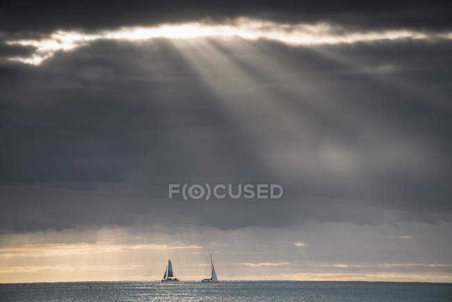 Distant view of yachts floating  in sea against dramatic sky with penetrating sun beams — Stock Photo