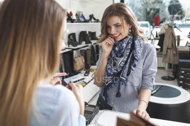 Mulher feliz olhando balconista segurando o cartão de crédito na loja de sapatos — Fotografia de Stock