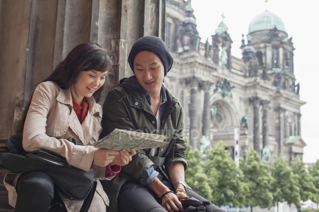 Vue en angle bas de jeunes amis lisant une carte au musée Altes contre la cathédrale de Berlin, Allemagne — Photo de stock