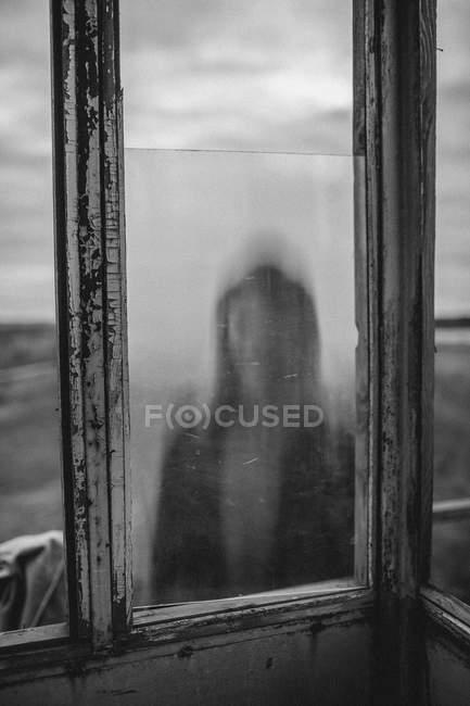 Разряженная девочка-подросток, которую видели через окно старой смотровой башни — стоковое фото