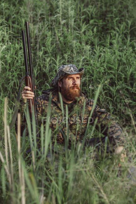 Rifle de cazador holding sentado en el campo de hierba - foto de stock