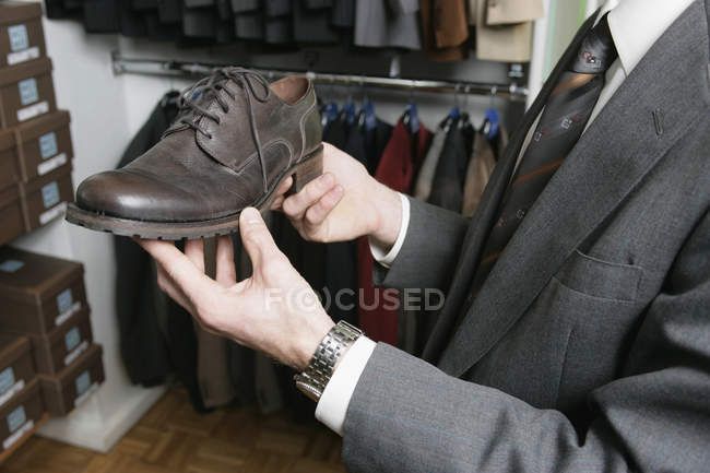 Hands of businessman holding shoe in retail store — Stock Photo
