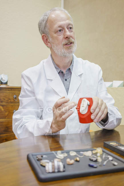 Doctor with anatomical model and hearing aids explaining at table in clinic — Stock Photo