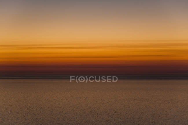 Scenic view of sea against orange sky during sunset — Stock Photo