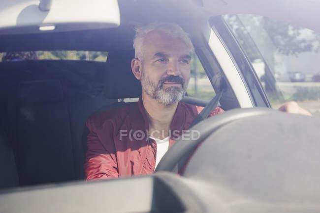 Mature man driving car seen through windshield — Stock Photo